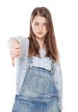 Den unga tonårs- flickan med tummen gör en gest ner isolerat arkivbild