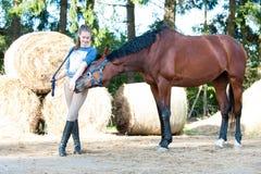 Den unga tonårs- flickan spelar med hennes favorit- kastanjebruna häst arkivfoton