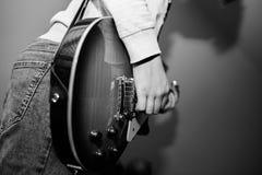 Den unga tonårs- pojken som spelar på den elektriska gitarren, fokus på pojkarna, räcker arkivbilder