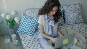 Den unga trendiga bloggeren skriver en ny artikel på ett bärbar datorsammanträde i säng stock video