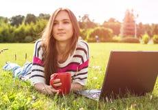Den unga trendiga kvinnan kopplar av, efter arbete med bärbara datorn i stad har parkerat royaltyfri fotografi