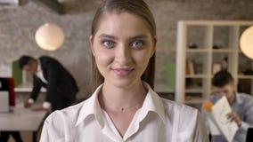 Den unga trevliga affärskvinnan håller ögonen på på kameran i regeringsställning och att le, hennes kollegor knyter kontakt med t arkivfilmer
