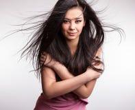 Den unga trevliga asiatiska flickan poserar i studio. Arkivbilder
