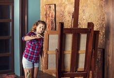 Den unga trevliga tonåringflickan böjer på molberten i konststudion royaltyfri fotografi