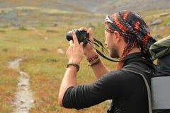 Den unga turist- grabben som är orakad, i en hatt och med struntsaker på hans händer och en ryggsäck på hans skuldror, gör ett fo royaltyfria foton