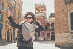 Den unga turist- kvinnan i hatt och solglasögon står på gatan av den europeiska staden och gör selfie på kamera för smartphone` s royaltyfri fotografi