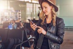 Den unga turist- kvinnan i hatt står på flygplatsen, använder smartphonen Hipsterflickan kontrollerar emailen och att prata som b Fotografering för Bildbyråer