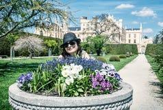 Den unga turist- kvinnan som poserar med blomsterrabatten, och Lednice rockerar in Royaltyfria Bilder