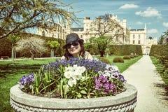 Den unga turist- kvinnan som poserar med blomsterrabatten, och Lednice rockerar in Fotografering för Bildbyråer