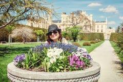 Den unga turist- kvinnan som poserar med blomsterrabatten, och Lednice rockerar, ye Arkivfoto