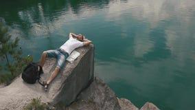 Den unga turist- mannen kopplar av, genom att vila på, vaggar nära lugna bergsjöyttersida med översikten som lägger bredvid honom lager videofilmer