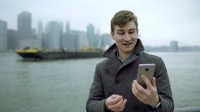 Den unga turisten gör den videopd översättningen nära Hudson River och pekar till en färja stock video