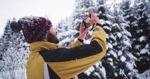 Den unga turisten som tar bilder av en snöig skog i vinterdagen, är han mycket imponerad vid all skönheten som han ser stock video