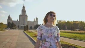 Den unga unga blonda flickan går lycklig på en varm sommarafton i parkera stock video