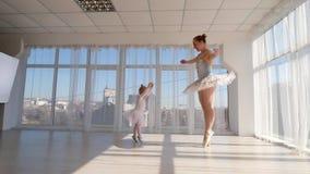 Den unga ursnygga ballerina undervisar liten dotterdans i studio lager videofilmer