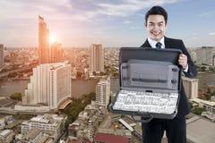 Den unga utövande mannen som rymmer ett bagage med sedeln på citys Royaltyfria Bilder
