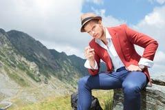 Den unga utomhus- mannen rymmer cigaretten i hand Royaltyfri Foto