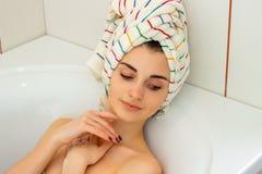 Den unga varma flickan med en handduk på hennes huvud ligger i badkaret som slokar ögon Arkivfoto