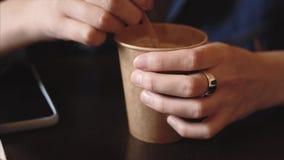 Den unga vegetariska flickan rör socker eller en stevia i en pappers- kopp med ett kaffe arkivfilmer
