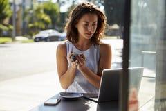 Den unga vita kvinnan med kaffe ser bärbara datorn utanför ett kafé Royaltyfria Bilder