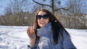Den unga vuxna flickan i svart solglasögon och rakt spela för mörkt hår kastar snöboll i parkerar utomhus i morgonen under lager videofilmer
