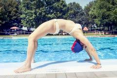 Den unga vuxna kvinnan i baddräkt gör gymnastik Arkivfoto