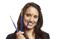 Den unga vuxna kvinnan vänder mot målare med målar borstar Royaltyfri Foto