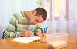 Den unga vuxna mannen kopplar in i självstudien, i rehabiliteringmitt Arkivfoto