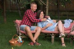 Den unga vuxna mannen och gravida kvinnan roar sig i garden royaltyfri foto