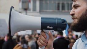 Den unga vuxna mannen ropar i megafon Det Caucasian folket ropar violently och ilsket arkivfilmer