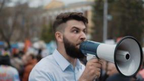 Den unga vuxna mannen ropar i megafon Det Caucasian folket ropar violently och ilsket stock video