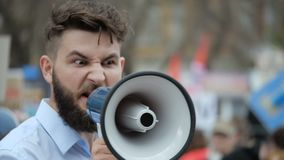 Den unga vuxna mannen ropar i megafon Det Caucasian folket ropar violently och ilsket lager videofilmer
