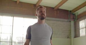 Den unga vuxna mannen som gör banhoppningstålar, övar under konditionsportgenomkörare Industriell stads- utbildning för Grunge 4K stock video