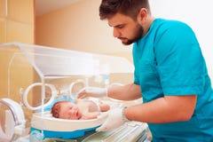 Den unga vuxna mannen som tar omsorg av nyfött, behandla som ett barn i begynnande kuvös Arkivbild