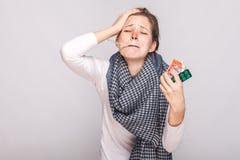 Den unga vuxna sjuka kvinnan har temperaturen som rymmer många preventivpillerar arkivbild