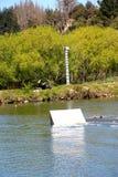 Den unga wakeboarderen som går stor av ett hopp på kabeln, parkerar Arkivfoto