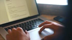 Den unga yrkesmässiga affärsmannen som använder den moderna bärbara datorn, närbild av mannen, räcker maskinskrivning på anteckni lager videofilmer