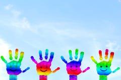 Den ungar målade handen för regnbågen för handkonst färgrika skrivar ut i himmelbakgrund royaltyfri bild
