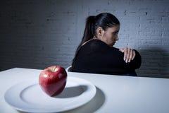 Den ungt kvinnan eller tonårigt med äpplefrukt på maträtt som symbol av galet bantar i näringoordning Arkivbild