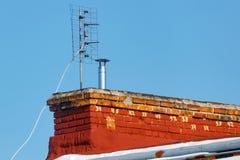 Den universella antennen för att motta den parallella TVsignalen installeras på taket av ett tegelstenhus Royaltyfri Bild