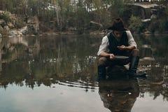 Den Unshavedgold grävaren tvättar guld i sjön med den steniga banken Royaltyfri Bild