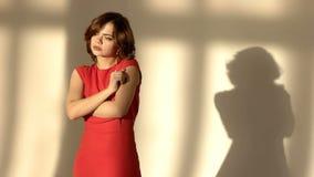 Den Unsmiling ledsna unga kvinnan satte hennes händer på tempel Den härliga flickan kramar sig på rummet Lady I Röd Det finns hen lager videofilmer