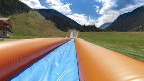 Den uppblåsbara vattenglidbanan i adrenalin parkerar royaltyfria bilder
