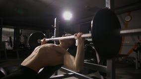 Den uppblåsta starka mannen med stora muskler lyfter stången som ligger på bänkslutet upp lager videofilmer