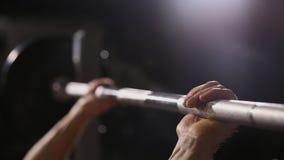 Den uppblåsta starka mannen med stora muskler lyfter stången som ligger på bänkslutet upp arkivfilmer