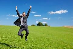 Den upphetsade affärsmannen hoppar högt i luften Arkivbild