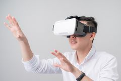 Den upphetsade asiatiska mannen i en VR rullar med ögonen och göra en gest med hans händer Royaltyfri Bild