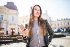 Den upphetsade flickadansen och lyssnande musik med hörlurar och ilar telefonen i gatan Royaltyfri Foto