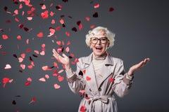 den upphetsade höga kvinnan med hjärta formade konfettier på st-valentindag, royaltyfri foto