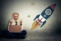 Den upphetsade höga mannen med höga riskabla mål uppsätta som mål arbete på bärbar datordatoren Royaltyfri Foto